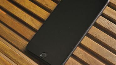 Black cellphone on a wooden table