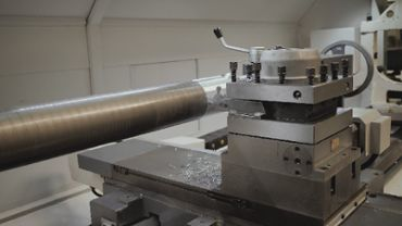 Lathe cutting a cylinder