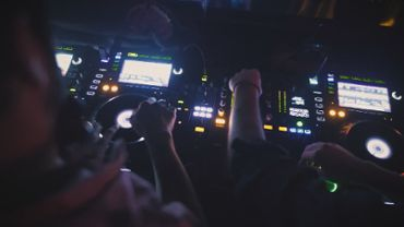 Two DJs mixing music at a nightclub