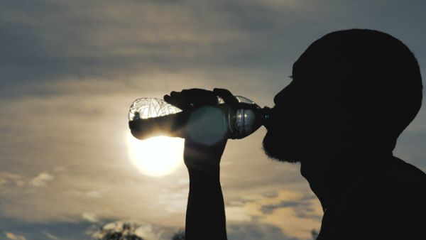 Silhouette of man drinking water
